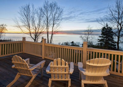 Deck w chairs overlooking lake sunset